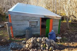 Painting the repaired cow byre door; neon orange mistake being tamed by a more sedate green