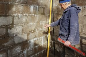 Mike is the electrician on this project and, as the lower-ground walls are now built, he can start the unpleasant task of channelling out the walls ready for light-switch and socket installation. First, he has to mark the positions...