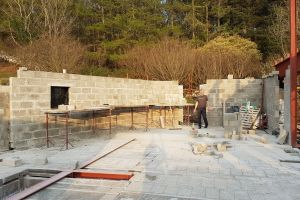 Mike stands in the eastern end of the upper ground floor, where the kitchen will be. As the walls go up, the unusual shape of the house becomes easier to see
