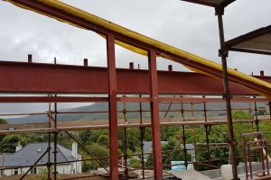 Before the roof timbers can be installed a wide strip of airtightness membrane is attached to the steel beam to act as a thermal barrier. As this can't be done in one continuous strip, Mike has to check that all joins and corners are properly taped and sealed