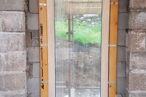 This will be the only east-facing window on the main living floor and is non-opening. It's held in place by wooden battens; the window reveals will be built up to it to hold it securely in place. The deep reveals will be splayed to help let in more light