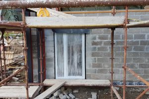 One of the lower-ground bedroom windows newly installed. The frames are clad externally in a dark grey aluminium, but the  protective coverings will be kept on until all the stone-cladding has been done and the scaffolding removed