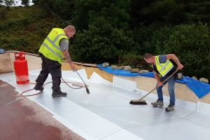 The membrane has an adhesive backing and must be applied to a dry roof. The roofers use a heat gun to dry the roof and also to help the adhesive stick. A soft broom is used to brush out any bubbles and wrinkles and smooth it down flat.